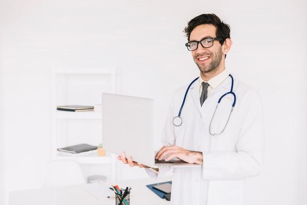 Ritratto di un medico maschio felice che per mezzo del computer portatile