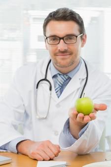Ritratto di un medico maschio sorridente che tiene una mela