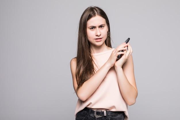 Ritratto di un microfono allegro della copertura della donna sullo smartphone isolato su una parete grigia