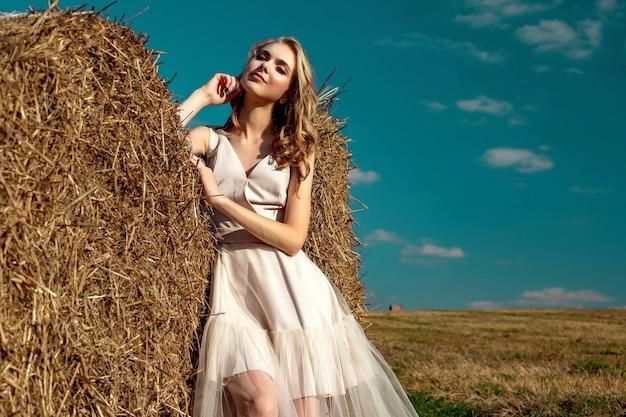 Ritratto di un modello biondo della ragazza che sta e posa un giorno soleggiato contro uno sfondo dei mucchi di fieno e del cielo blu