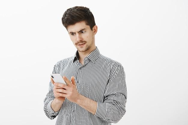 Ritratto di un modello maschio europeo ordinario intenso e confuso con i baffi, che guarda interrogato sullo schermo dello smartphone, riceve un messaggio strano o non sa dove sono finiti i soldi dal conto bancario
