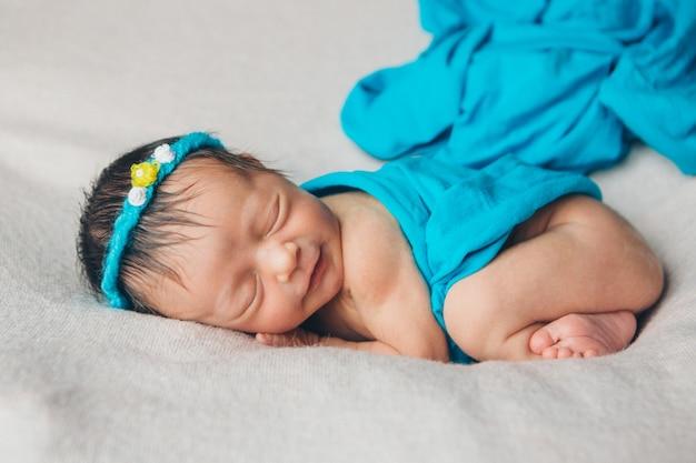 Ritratto di un neonato addormentato in una fascia con fiore. concetto di salute: fecondazione in vitro, accessori per bambini