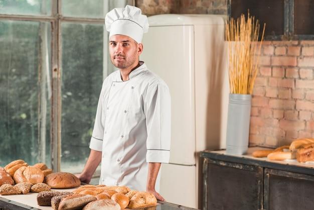 Ritratto di un panettiere maschio con vari pani al forno