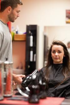 Ritratto di un parrucchiere maschile che soffia i capelli