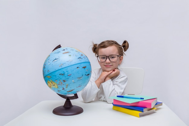 Ritratto di un piccolo allievo con gli occhiali seduto a un tavolo su un bianco isolato