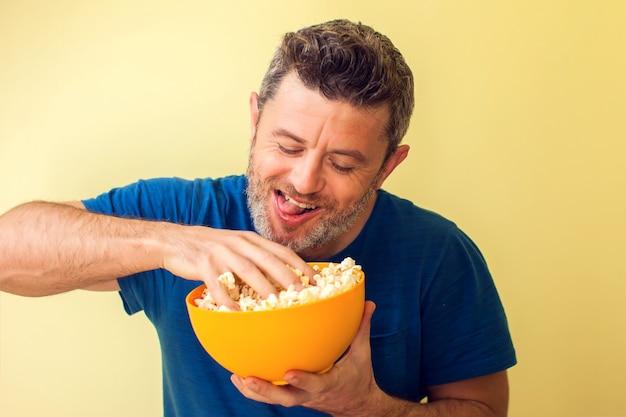Ritratto di un popcorn mangiatore di uomini divertente isolato