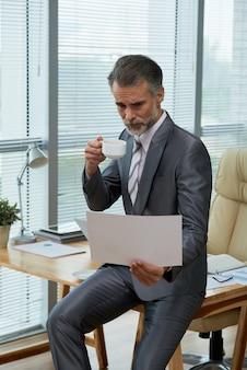 Ritratto di un potente ceo che si appollaia sulla scrivania sfogliando il rapporto e sorseggiando un caffè