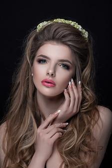 Ritratto di un primo piano della ragazza con stile di capelli, manicure e trucco piacevoli. la corona di fiori adorna la sua testa