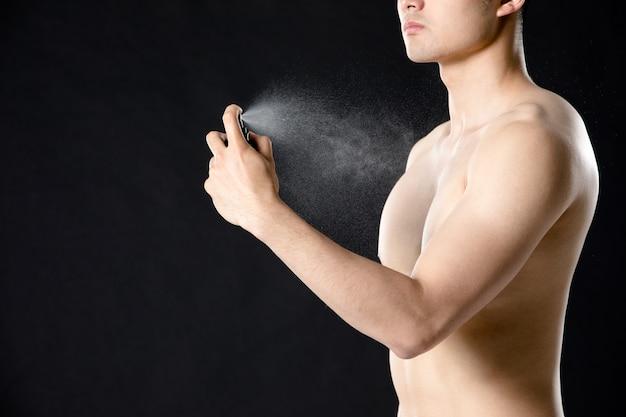 Ritratto di un profumo di spruzzatura di un uomo mezzo nudo bello