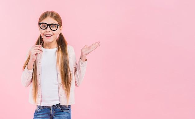 Ritratto di un puntello felice degli occhiali della tenuta della ragazza che scrolla le spalle contro il fondo rosa