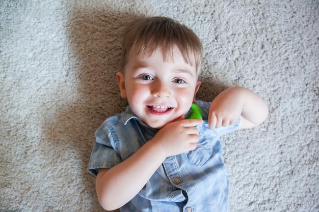 Ritratto di un ragazzino biondo sfacciato sul pavimento di moquette a casa ridendo e divertendosi.