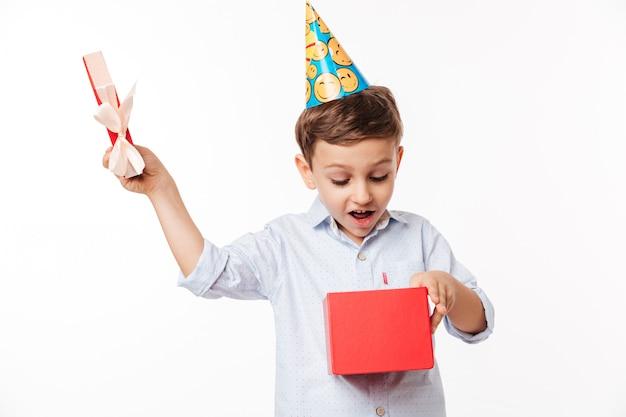 Ritratto di un ragazzino carino eccitato in un cappello di compleanno