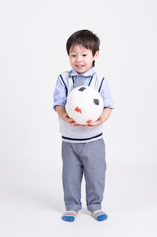 Ritratto di un ragazzino in piedi con pallone da calcio sorridente in mano