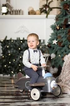 Ritratto di un ragazzino seduto su un aeroplanino giocattolo vintage vicino a un albero di natale. decorazioni natalizie. il ragazzo si rallegra del suo regalo di natale. buon natale e felice anno nuovo