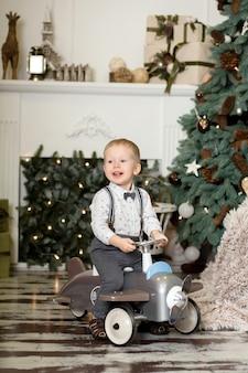 Ritratto di un ragazzino seduto su un aeroplanino giocattolo vintage vicino a un albero di natale