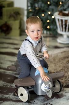 Ritratto di un ragazzino seduto su un aeroplanino giocattolo vintage vicino a un albero di natale.