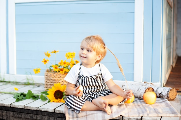 Ritratto di un ragazzino sorridente seduto su un portico in legno a casa in una giornata autunnale. concetto di infanzia. un bambino gioca nel cortile in autunno. bambino felice. raccolta. piccolo contadino. bambino affascinante