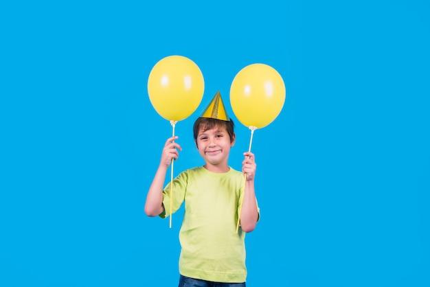 Ritratto di un ragazzino sveglio che tiene i palloni gialli contro il contesto blu