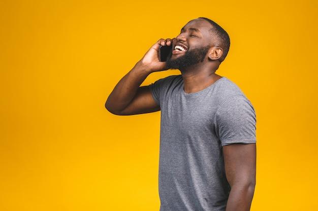 Ritratto di un ragazzo afroamericano felice che parla sul telefono cellulare.