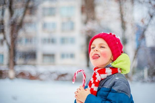 Ritratto di un ragazzo allegro con la lecca-lecca di natale in mani su una via di inverno.