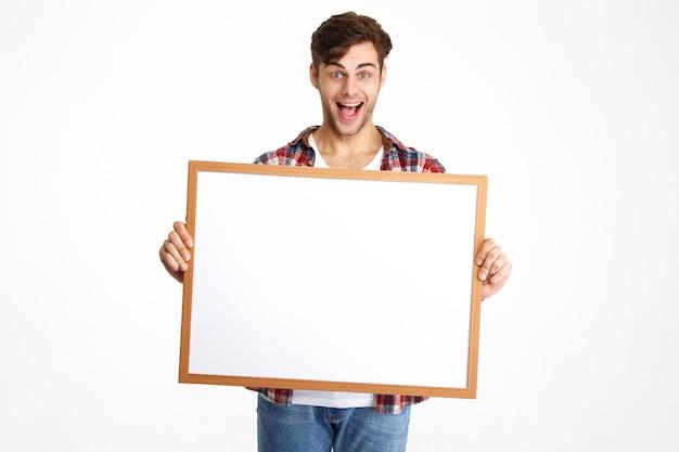 Ritratto di un ragazzo allegro eccitato tenendo bordo bianco