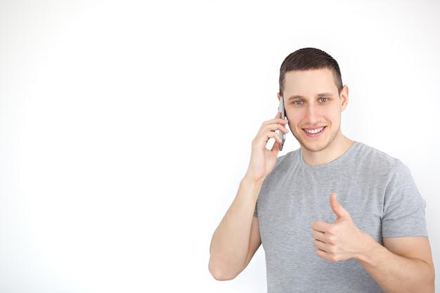 Ritratto di un ragazzo allegro, positivo, attraente con setole in una maglietta grigia, con uno schermo nero in mano, mostrando un pollice in alto gesto