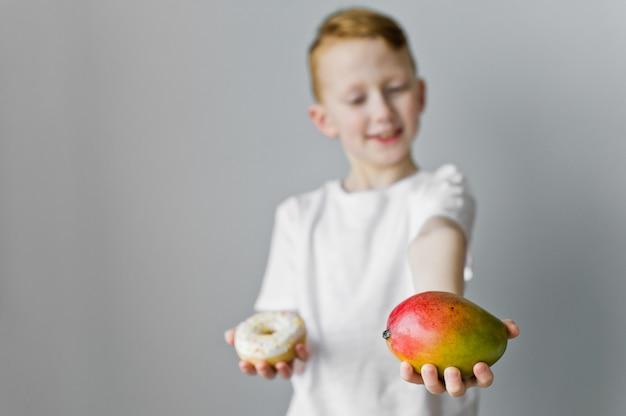 Ritratto di un ragazzo bambino confuso scegliendo tra ciambella e mango su sfondo grigio