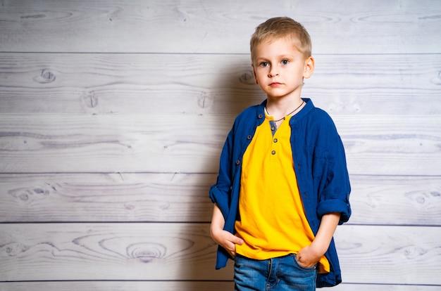 Ritratto di un ragazzo bellissimo bambino in maglietta gialla e giacca di jeans, camicia. ragazzo che sta su un fondo di legno bianco.