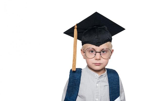 Ritratto di un ragazzo biondo carino in grandi occhiali, cappello accademico e una borsa di scuola.