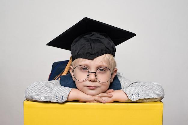 Ritratto di un ragazzo biondo carino in grandi occhiali, cappello accademico e uno zaino. sfondo bianco.