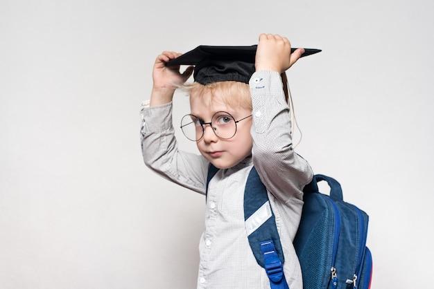 Ritratto di un ragazzo biondo con gli occhiali, un cappello accademico e una cartella su uno sfondo bianco. concetto di scuola