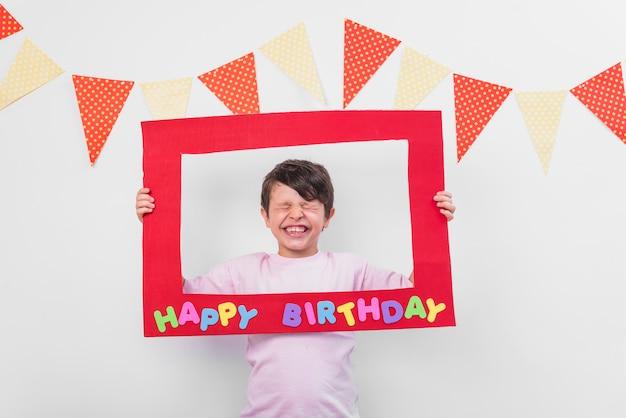 Ritratto di un ragazzo carino tenendo la cornice di compleanno con gli occhi chiusi