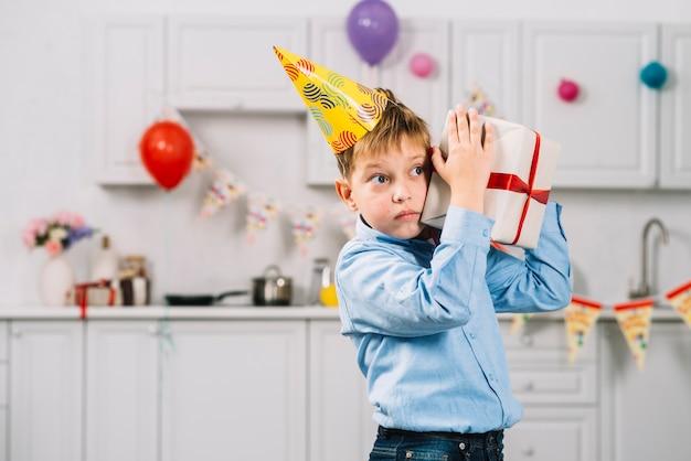Ritratto di un ragazzo che scuote il regalo di compleanno in cucina