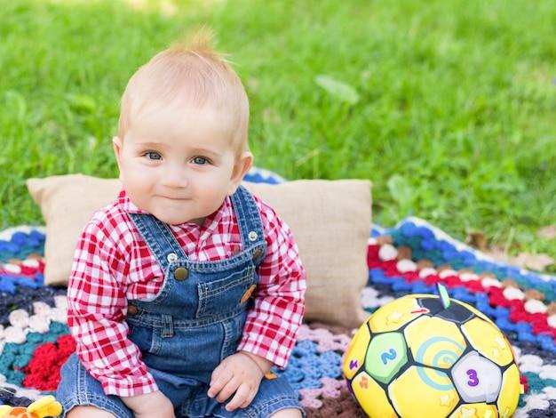 Ritratto di un ragazzo che si siede su una coperta su un'erba fresca in un parco cittadino in estate