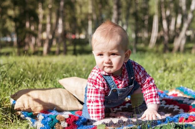 Ritratto di un ragazzo che si siede su una coperta su un'erba fresca in un parco della città di estate