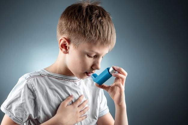 Ritratto di un ragazzo che utilizza un inalatore per l'asma per il trattamento di malattie infiammatorie, mancanza di respiro. il concetto di trattamento per tosse, allergie, malattie del tratto respiratorio.