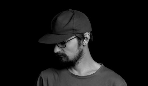 Ritratto di un ragazzo con la barba con gli occhiali e un berretto su sfondo nero