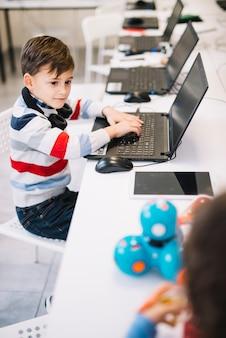 Ritratto di un ragazzo con laptop guardando bambino che gioca con il giocattolo in classe