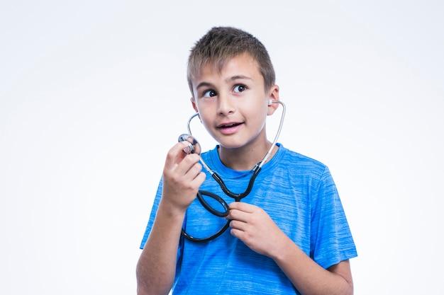 Ritratto di un ragazzo con stetoscopio su sfondo bianco