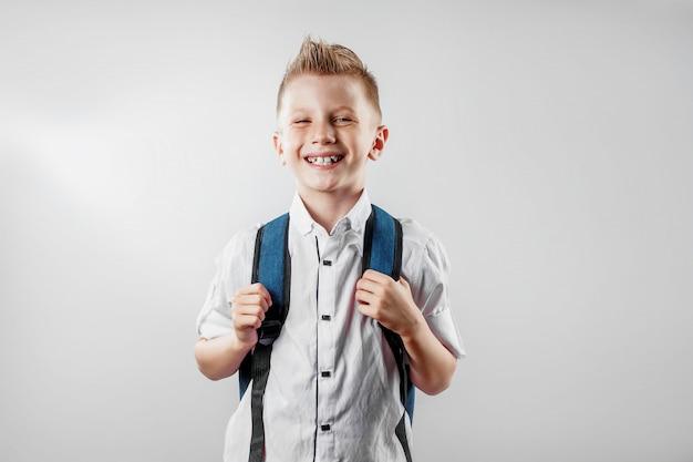 Ritratto di un ragazzo di una scuola elementare su uno sfondo chiaro
