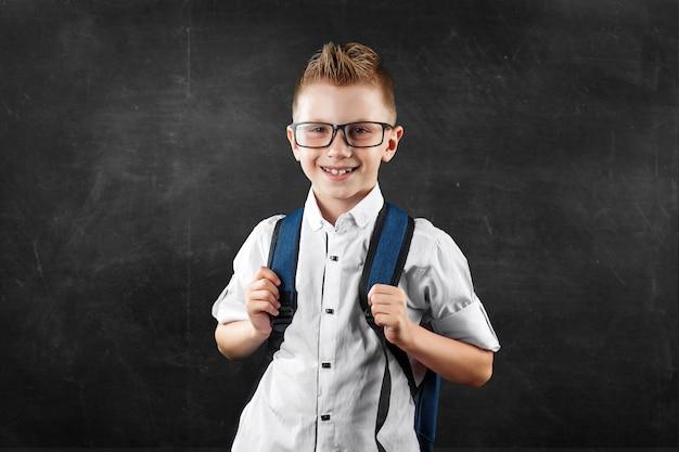 Ritratto di un ragazzo di una scuola elementare su uno sfondo di un consiglio scolastico