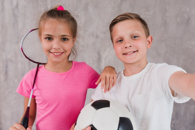 Ritratto di un ragazzo e una ragazza giocatori con la racchetta e pallone da calcio davanti al muro di cemento