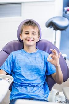 Ritratto di un ragazzo felice che si siede sulla sedia dentale che gesturing segno giusto