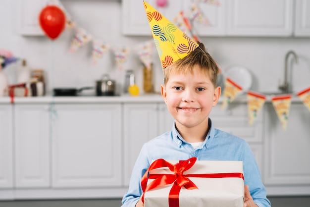 Ritratto di un ragazzo felice che tiene regalo di compleanno in cucina