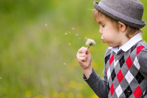 Ritratto di un ragazzo in un cappello in piedi su uno sfondo di alberi in fiore.