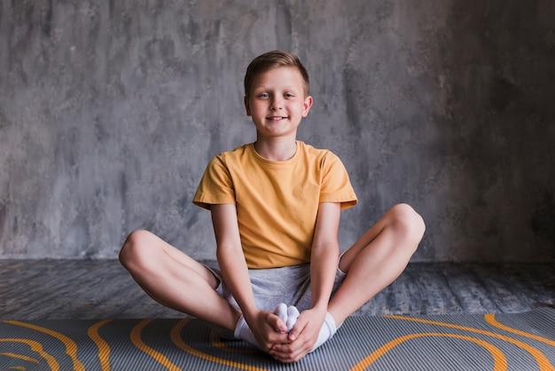 Ritratto di un ragazzo sorridente che si siede sulla stuoia di esercizio che guarda l'obbiettivo