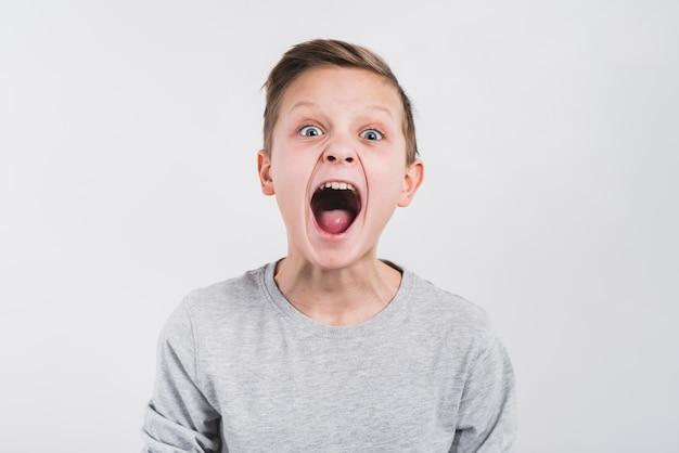 Ritratto di un ragazzo urlando rumorosamente contro sfondo grigio