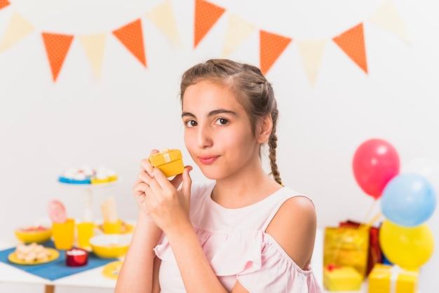 Ritratto di un regalo di partecipazione ragazza durante la festa di compleanno