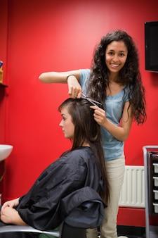 Ritratto di un taglio di capelli femminile felice parrucchiere