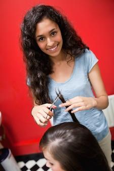 Ritratto di un taglio di capelli parrucchiere femminile sorridente